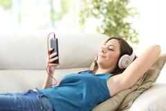 Música que escucha de la muchacha que miente en el sofá Imágenes de archivo libres de regalías
