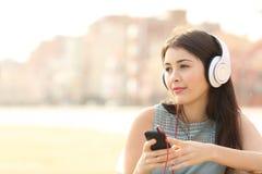 Música que escucha de la muchacha sincera con un smartphone Fotografía de archivo