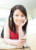 Música que escucha de la mujer alegre con los auriculares en lyi Fotografía de archivo