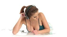 Música que escucha de la mujer atractiva hermosa joven en auriculares estéreos grandes metrajes