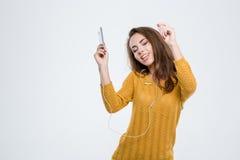 Música que escucha de la mujer bonita en auriculares Imagen de archivo libre de regalías
