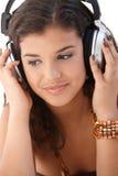Música que escucha de la mujer bonita a través de los auriculares Imágenes de archivo libres de regalías