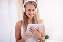 Música que escucha de la mujer con auriculares y usar una PC de la tableta en a Fotografía de archivo
