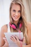 Música que escucha de la mujer con auriculares y usar una PC de la tableta en a Imágenes de archivo libres de regalías