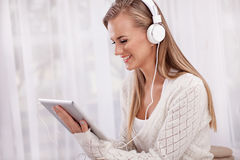 Música que escucha de la mujer con auriculares y usar una PC de la tableta en a Imagen de archivo