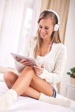 Música que escucha de la mujer con auriculares y usar una PC de la tableta en a Foto de archivo