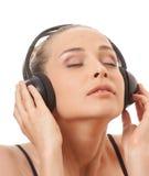 Música que escucha de la mujer con los auriculares, en blanco Imágenes de archivo libres de regalías