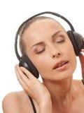 Música que escucha de la mujer con los auriculares, en blanco Foto de archivo libre de regalías