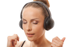 Música que escucha de la mujer con los auriculares, en blanco Imagenes de archivo