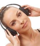 Música que escucha de la mujer con los auriculares, en blanco Imagen de archivo