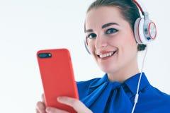 Música que escucha de la mujer con los auriculares de un teléfono elegante Fotos de archivo libres de regalías
