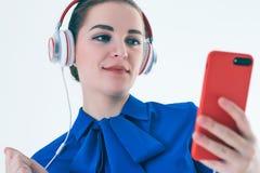 Música que escucha de la mujer con los auriculares de un teléfono elegante Fotografía de archivo