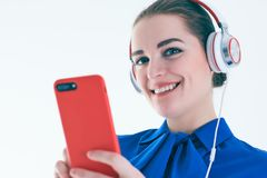 Música que escucha de la mujer con los auriculares de un teléfono elegante Fotografía de archivo libre de regalías