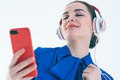 Música que escucha de la mujer con los auriculares de un teléfono elegante Imagen de archivo