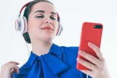 Música que escucha de la mujer con los auriculares de un teléfono elegante Imagenes de archivo