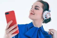 Música que escucha de la mujer con los auriculares de un teléfono elegante Foto de archivo libre de regalías
