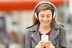 Música que escucha de la mujer con los auriculares y el teléfono Fotos de archivo libres de regalías