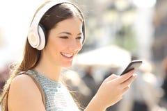 Música que escucha de la mujer de un teléfono elegante en la calle Fotos de archivo libres de regalías