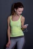 Música que escucha de la mujer deportiva joven con el teléfono sobre gris Fotos de archivo libres de regalías