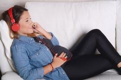 Música que escucha de la mujer embarazada en el sofá Imagen de archivo