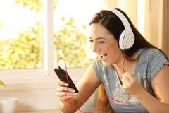 Música que escucha de la mujer emocionada con los auriculares Imagen de archivo
