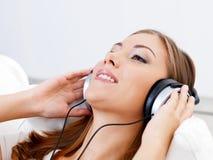 Música que escucha de la mujer en auricular Imágenes de archivo libres de regalías