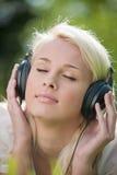 Música que escucha de la mujer en auriculares Imagen de archivo