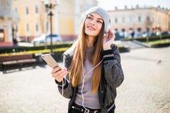 Música que escucha de la mujer en línea con los auriculares inalámbricos de un smartphone en la calle en un día soleado del veran Foto de archivo