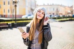 Música que escucha de la mujer en línea con los auriculares inalámbricos de un smartphone en la calle en un día soleado del veran Imagen de archivo