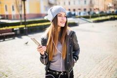 Música que escucha de la mujer en línea con los auriculares inalámbricos de un smartphone en la calle en un día soleado del veran Imágenes de archivo libres de regalías