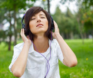 Música que escucha de la mujer en la naturaleza Foto de archivo libre de regalías