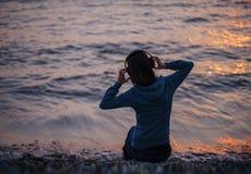 Música que escucha de la mujer en la playa en puesta del sol Fotos de archivo
