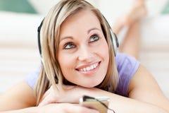 Música que escucha de la mujer encantadora que miente en el suelo Imagen de archivo libre de regalías