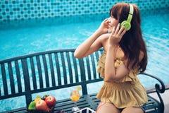 Música que escucha de la mujer eufórica con el auricular y la consumición de la manzana roja al lado del swimmimngpool, feliz imagen de archivo libre de regalías