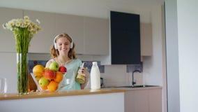 Música que escucha de la mujer feliz con smartphone en cocina Muchacha feliz almacen de video