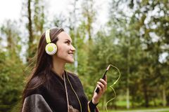 Música que escucha de la mujer feliz joven del smartphone con los auriculares en un parque reservado Fotos de archivo libres de regalías