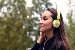 Música que escucha de la mujer feliz joven del smartphone con los auriculares en un parque reservado Imagen de archivo libre de regalías