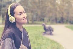 Música que escucha de la mujer feliz joven del smartphone con los auriculares en un parque reservado Foto de archivo