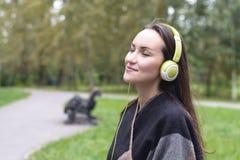 Música que escucha de la mujer feliz joven del smartphone con los auriculares en un parque reservado Imágenes de archivo libres de regalías