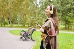 Música que escucha de la mujer feliz joven del smartphone con los auriculares en un parque reservado Fotografía de archivo
