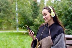 Música que escucha de la mujer feliz joven del smartphone con los auriculares en un parque reservado Fotografía de archivo libre de regalías