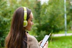 Música que escucha de la mujer feliz joven del smartphone con los auriculares en un parque reservado Fotos de archivo