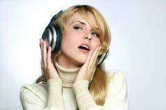Música que escucha de la mujer hermosa en auriculares Imagenes de archivo
