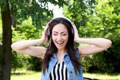 Música que escucha de la mujer hermosa joven con los auriculares en el par Imagen de archivo