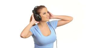 Música que escucha de la mujer hermosa joven en auriculares estéreos grandes metrajes