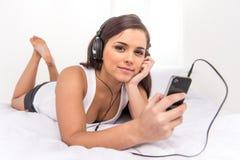 Música que escucha de la mujer hermosa que miente en cama en casa Imágenes de archivo libres de regalías