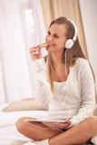 Música que escucha de la mujer joven con auriculares en dormitorio Imágenes de archivo libres de regalías
