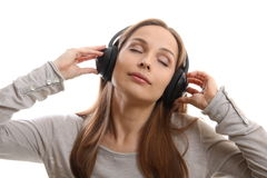Música que escucha de la mujer joven con los auriculares Fotos de archivo libres de regalías