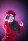 Música que escucha de la mujer joven con los auriculares Imagenes de archivo