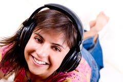 Música que escucha de la mujer joven con los auriculares Imágenes de archivo libres de regalías